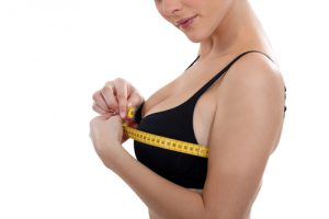 A woman in a black bra measuring her bust with a yellow measuring tape on a white background