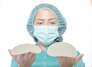 Surgeon holding breast implants of different sizes