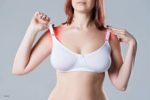 Woman experiencing pain in her shoulders from the weight of her bra straps.
