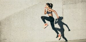 Women in athletic clothing exercising outside on sidewalk.