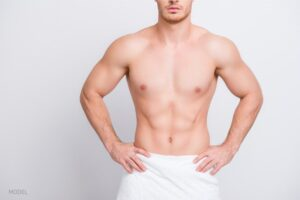 Shirtless man without gynecomastia standing with hands on hips.