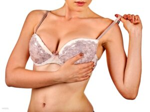 Woman with hand lifting up breast over lacy bra.