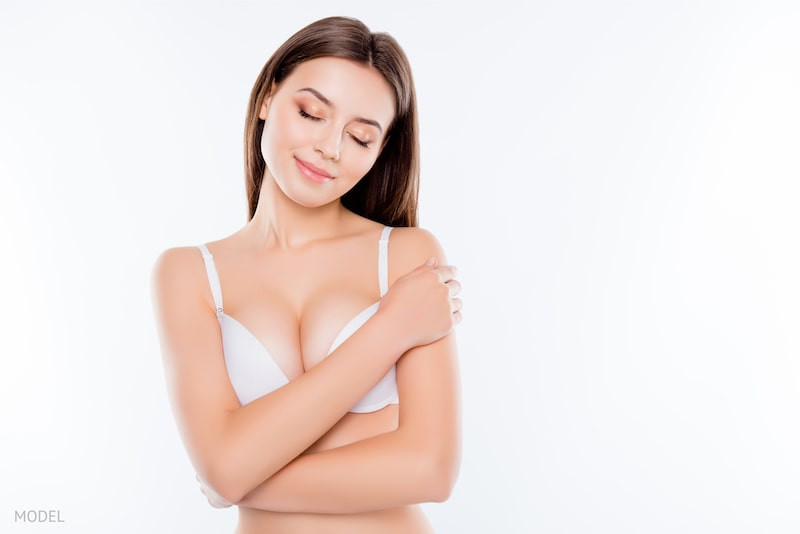 Woman wrapping her arms around her breasts, showing breast love and contentment.