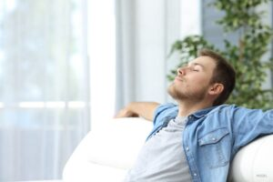 Man relaxing on couch with outstretched arms.