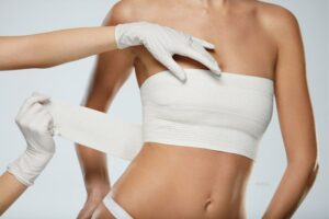 Woman wrapping her breasts with gauze after surgery.