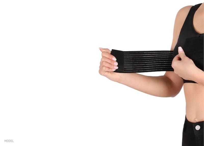 Woman fastening black compression bra around her breasts.