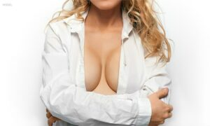 Woman wearing open button-up shirt, exposing some of the breasts
