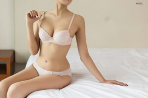 Woman sitting on bed wearing bra and underwear.
