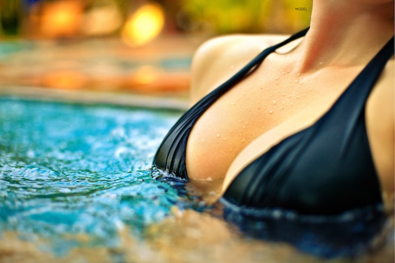 Close-up image of woman's breasts in a bikini coming out of pool