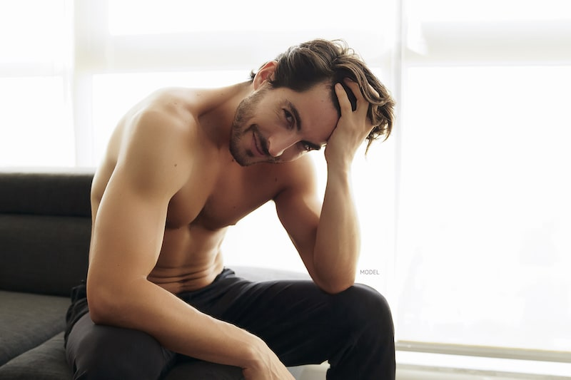 Shirtless man running his hand through his hair, sitting on couch.