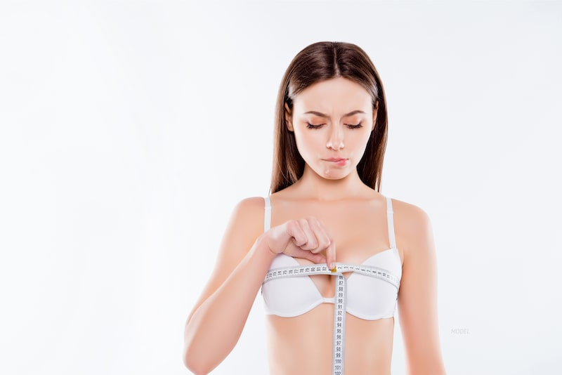 Young woman wrapping tape measure around her bust, looking frustrated.