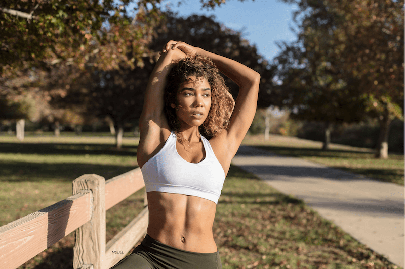 Woman in sports bra stretching at park